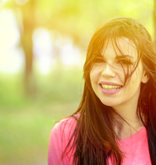 Portrait close up of young beautiful smiling woman in nature