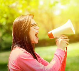 Portrait of middle aged woman shouting using megaphone against a