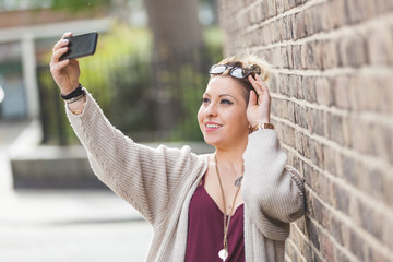 Hipster woman taking a selfie against brick wall in London.