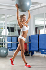 Pretty woman with ball in the gym