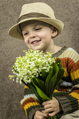 boy holding flowers snowdrops