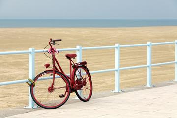 rotes fahrrad an der strandpromenade