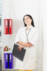 Portrait of doctor woman with clipboard in office