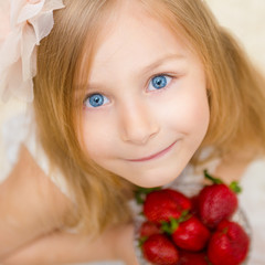 Portrait of a beautiful little girl with strawberry