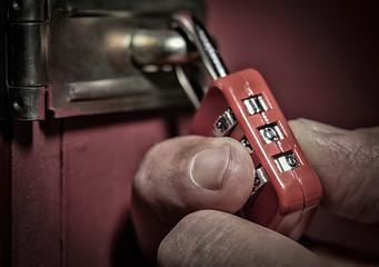 burglar trying to unlock combination lock