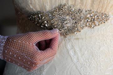 Mano di sposa e particolare del vestito
