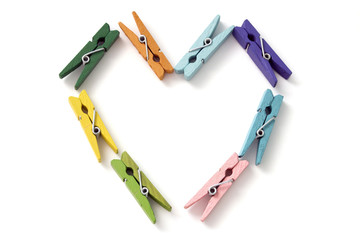 the heart of a number of colored linen clothespins isolated