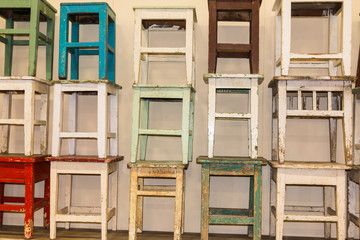 A bunch of worn and colorful stacked stools