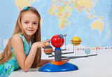 Young girl study solar system in science class