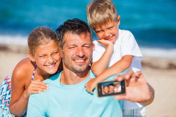 Father and his kids at beach taking selfie
