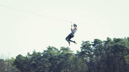 Woman sliding on a zip line in an adventure park, slow motion