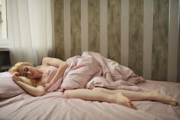 Beautiful young woman sleeps in the bedroom