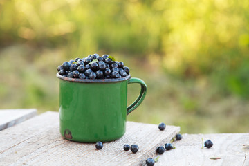 Ripe wild blueberries in the old green mug on the wooden table