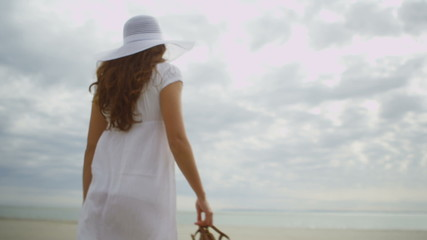 Young woman walks onto the beach in slow motion