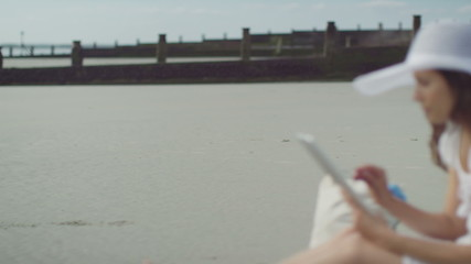 Woman on a beach using her tablet device in slow motion