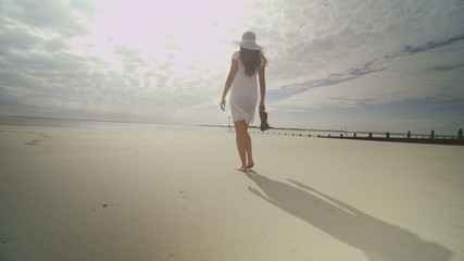 Woman walks on a beach on a nice day holding her shoes