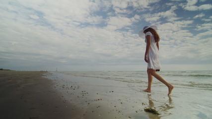 Woman walks along the shore of a beach