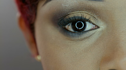 4K close up image of black woman eye against gray background
