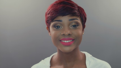 Beautiful African woman with pink lips turns with a look into