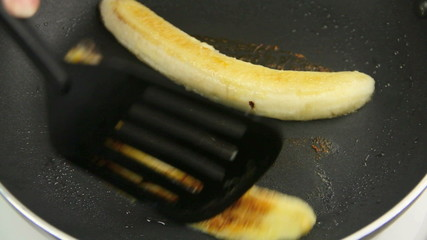 Banana being put into a pan with a spatula to fry.