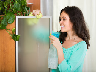 Woman dusting glass of furniture