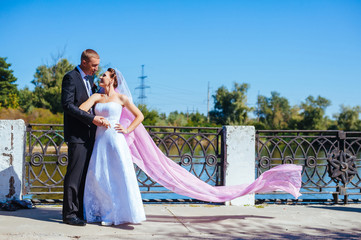 newly married couple.wind lifting long white bridal veil. bride