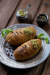 Hasselback potatoes with fresh pesto sauce, studio shot