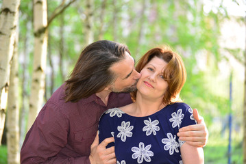 Man kissing a woman on the cheek in  park