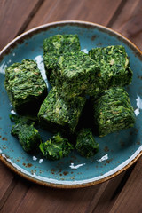 Close-up of spinach cubes on a turquoise plate, selective focus