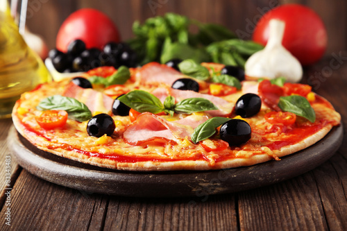 Plakat Delicious fresh pizza on brown wooden background