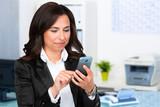 businessfrau schaut auf ihr mobiltelefon
