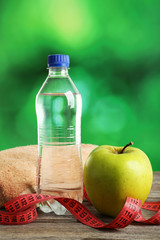 Green apple with measuring tape and bottle of water