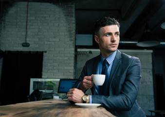 Pensive businessman drinking coffee in cafe