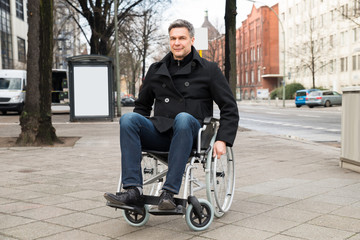 Disabled Man On Wheelchair In City