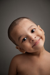 Close up of naughty indian baby boy smiling over grey background