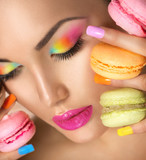 Beauty model girl taking colorful macaroons