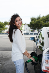 cheerful young woman filling car fuel at gas station