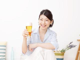 部屋でビールを飲む女性