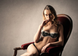Sensual woman sitting on a red chair