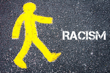 Yellow pedestrian figure walking towards RACISM