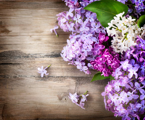 Lilac flowers bunch over wooden background
