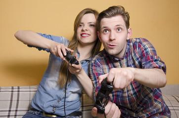 Cute young couple playing video games, having fun