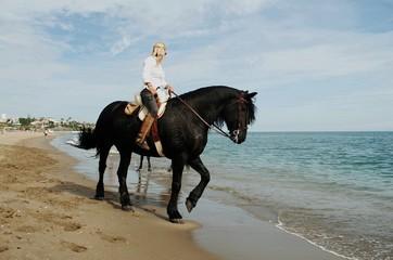 Mujer a caballo por la playa