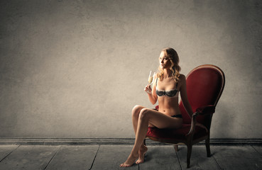 Girl in lingerie sitting in a red chair