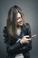 Smiling young girl looking at phone with amused emotion on her f