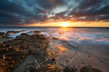 Early morning landscape of ocean over rocky shore and glowing su