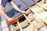 le couvreur pose les tuiles sur le toit - 83370829