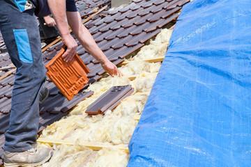 le couvreur pose les tuiles sur le toit