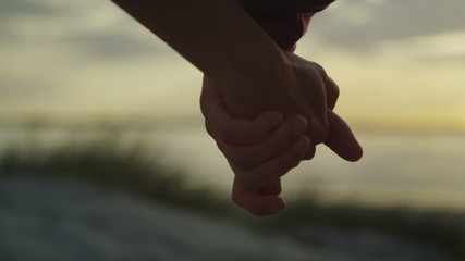 Couple holding hands at the beach at sunset in slow motion
