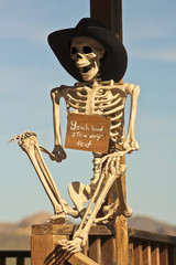 A Cowboy Skeleton Sits Against a Post